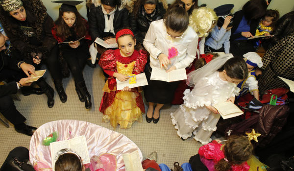Jews celebrating Purim -dressing up and reading the book of Esther